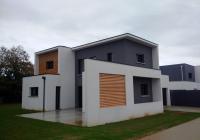 Vue facade sur voie avec mur brise vue béton et bois